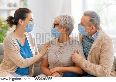 Adult daughter and senior parents wearing facemasks during coronavirus and flu outbreak. Virus and illness protection, home quarantine. COVID-2019