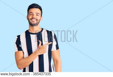 Young handsome hispanic man wearing striped tshirt cheerful with a smile of face pointing with hand and finger up to the side with happy and natural expression on face