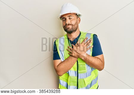 Handsome man with beard wearing safety helmet and reflective jacket smiling with hands on chest, eyes closed with grateful gesture on face. health concept.