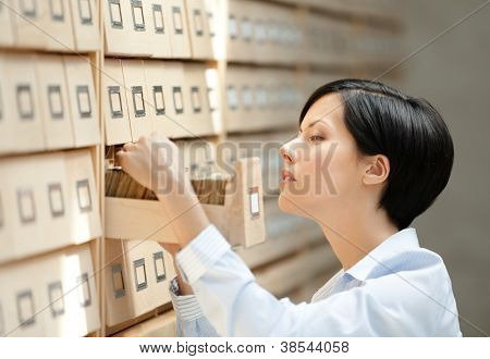 Woman searches something in card catalog composed of set of wood boxes at the library. Information
