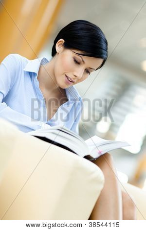 Business woman rests at the sofa reading interesting book at the hall