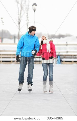 Young couple holding hands iceskating outdoors on a frozen lake or open-air rink against a snowy winter landscape