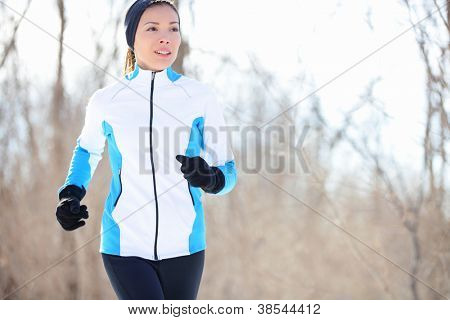 Running young Asian woman jogging in a winter fleece and gloves in open countryside with copyspace in a health and fitness concept poster