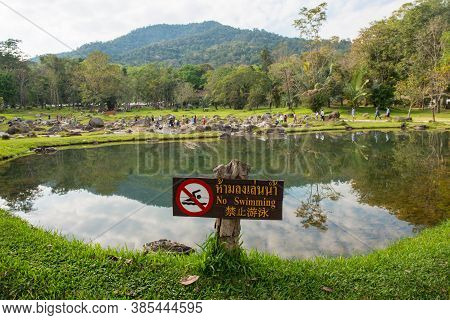 The Large Pool In Chae Son National Park With Warning Wooden Sign In Lampang Province Of Thailand. (