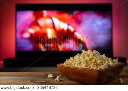 A Wooden Bowl Of Popcorn And Remote Control In The Background The Tv Works. Evening Cozy Watching A