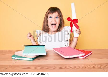 Little caucasian kid girl with long hair holding graduate degree diploma for preschool pointing thumb up to the side smiling happy with open mouth