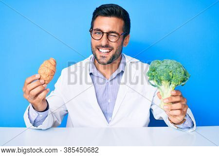 Young hispanic man as nutritionist doctor holding croissant and broccoli winking looking at the camera with sexy expression, cheerful and happy face.