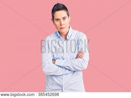Young woman with short hair wearing business clothes skeptic and nervous, disapproving expression on face with crossed arms. negative person.