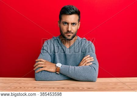Handsome hispanic man wearing casual style sitting on the table skeptic and nervous, disapproving expression on face with crossed arms. negative person.