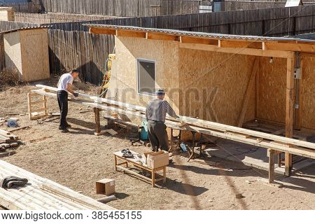 Two Male Workers Prepare Wooden Planks For Construction On A Sawmill. Construction Carpentry. Fasten