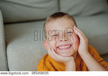 Autumn Portrait Of A Little Cute Boy In An Orange Sweater. Cozy Portrait Of A Boy Sitting At Home. F