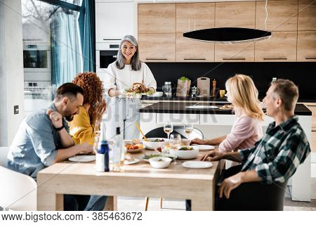 Happy Guests Are Sitting At The Dining Table