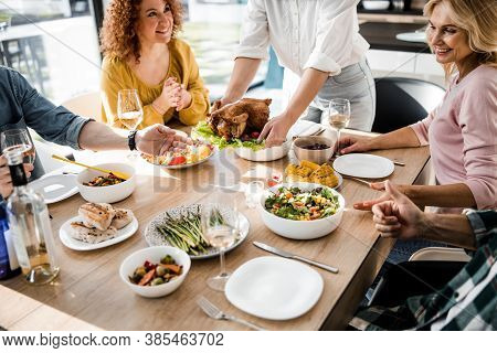 Woman Putting Food On The Festive Table For Her Guests