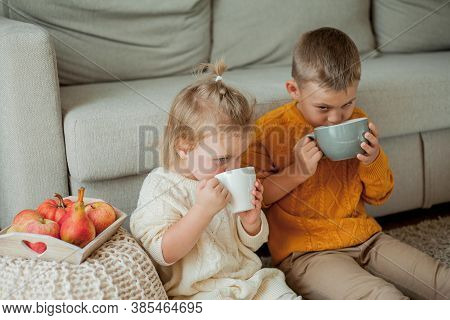 Little Brother And Sister In Cozy Knitted Sweaters Are Drinking Tea At Home. Portrait Of Cute Little
