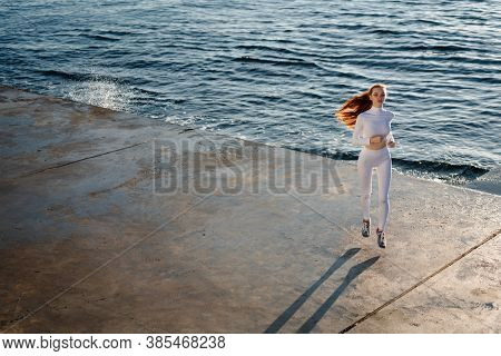 Image of redhead focused sportswoman running while working out on promenade at sunrise