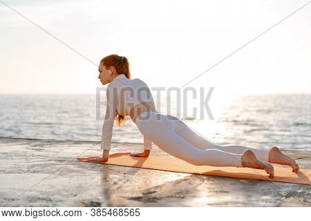 Image of redhead sportswoman in earphones doing yoga exercise while working out on promenade at sunrise