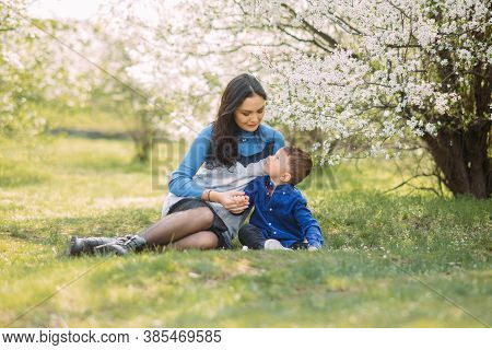 Happy Mother And Son Sit And Rest In Green Grass On Sunlit Glade Against Background Of Blooming Spri
