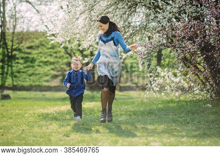 Happy Mother And Son Run And Have A Fun On Sunlit Glade Against Background Of Blooming Spring Garden