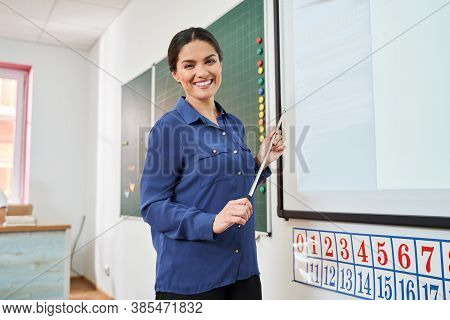 Merry Female Teacher Enjoying Working Day In Class Room