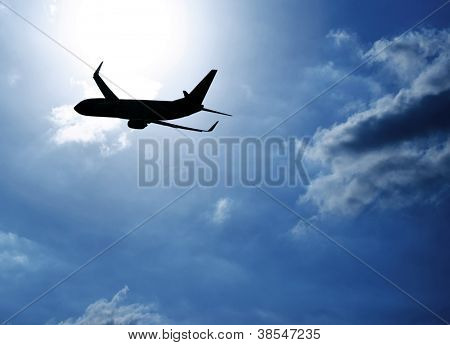Picture of silhouette airplane in blue sky, journey trip, airliner in heaven, plane over clouds background, air transportation, luxury airline, business destination, fast flight, tourism concept