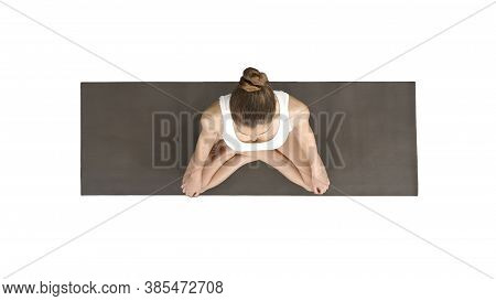 Young Sporty Woman Practicing Yoga Sitting In Lotus Pose And Breathing Deeply On White Background.