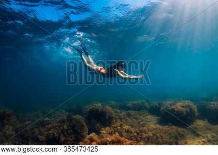 Freediver Slim Woman In Bikini Glides In Blue Sea And Sun Rays.