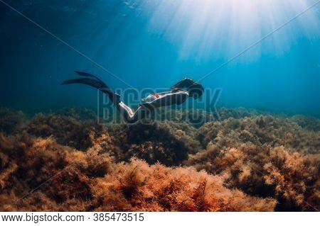 Freediver Slim Woman In Bikini Glides In Blue Sea And Sun Rays. Freediving With Fins Underwater In O