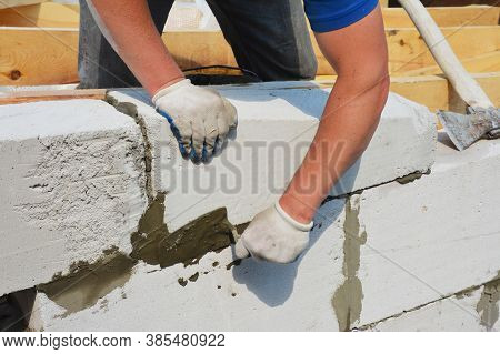 A Building Contractor Is Constructing A Wall From Autoclaved Aerated Concrete Blocks Using A Trowel