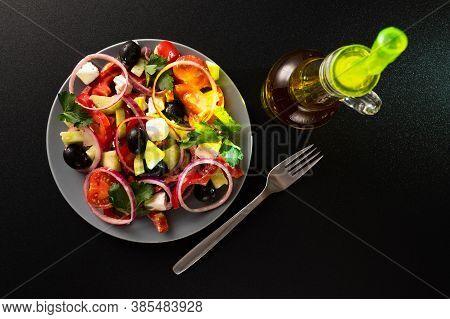 Plate With Greek Salad And Fork. Greek Salad And Dark Background. Bottle Of Olive Oil.