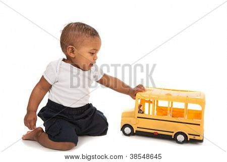 Little African American Baby Boy Pushing Toy School Bus on White Background
