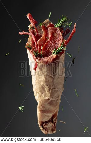 Slices Of Spicy Dry-cured Meat Sprinkled With Rosemary In A Paper Bag On A Dark Background.