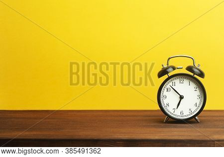 Vintage Alarm Clock On A Yellow Background. Black Alarm Clock Showing Morning Time On The Table. Tim