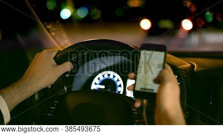 Male Hands On Steering Wheel, Backseat Shot With View On Road At Night. Hands On Wheel With Smartpho