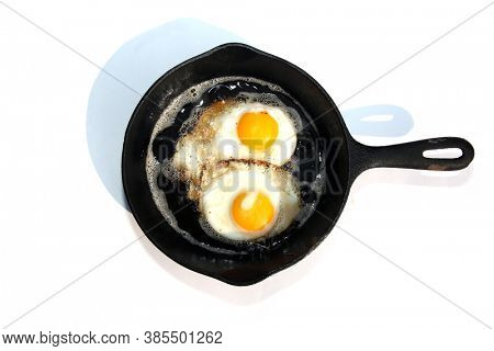 Cast Iron Frying Pan. Eggs being cooked in a Cast Iron Skillet. Frying Pan with cooked eggs on a white background with shadows.