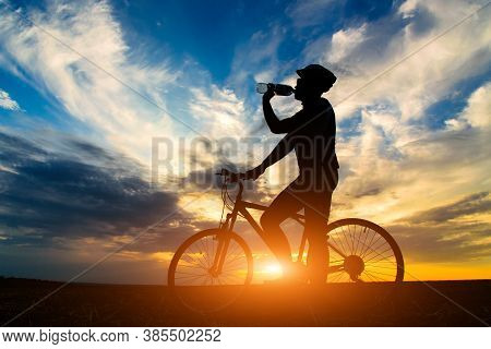 Silhouette Of A Cyclist Against The Sunset. Cyclist Drink Water Have A Rest.