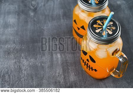 Iced Pumpkin Cocktails In Glass Jars Decorated With Scary Faces On The Chalkboard. Halloween Party M