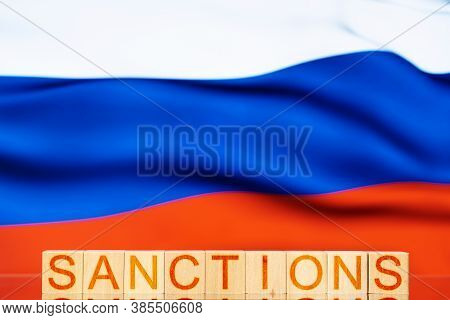 Sanctions. Wooden Blocks With The Inscription Sanctions On The Background Of The Flag Of Russia