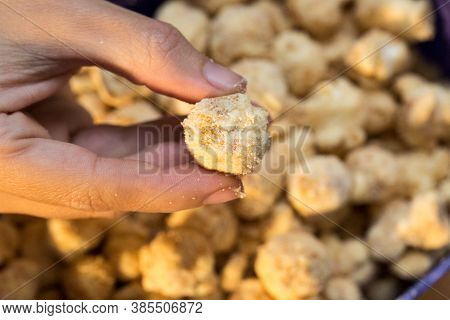 Hand Holding Gourmet White Chocolate Popcorn And Gourmet Peanuts With Blurred Background.