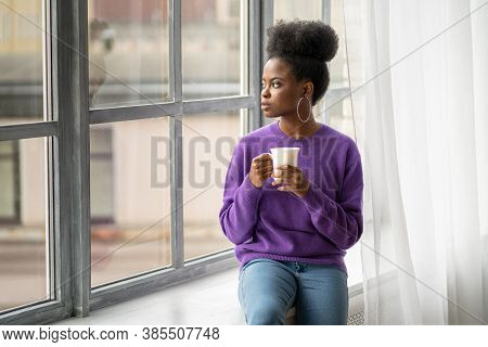 Pensive African American Millennial Biracial Woman With Trendy Jewelry Earrings Wear Purple Sweater