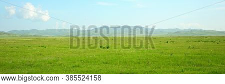 Panoramic Shot Of A Picturesque Valley Flooded With Bright Sunlight.