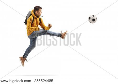 Full length profile shot of a male teenager jumping and kicking a soccer ball isolated on white background
