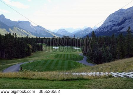 Gorgeous Par 3 On A Golf Course Surrounded By Forest And Big Mountains In The Background, On A Beaut