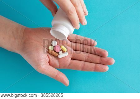 Many Pills Are Poured From A Medicine Bottle. Pills And Pills On A Blue Background. Medical Tablets: