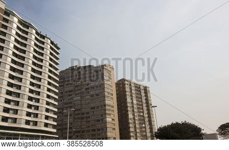 Upward View Of Tall Residential Buildings Against Blue Sky