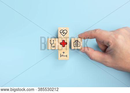 Health Medical Insurance Concept, Hand Arranging Wood Cube With Medical Symbol On Pastel Blue Backgr