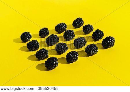Blackberries Isolated On Illuminating Yellow Background. Trendy Creative Concept. Summer Juicy Black
