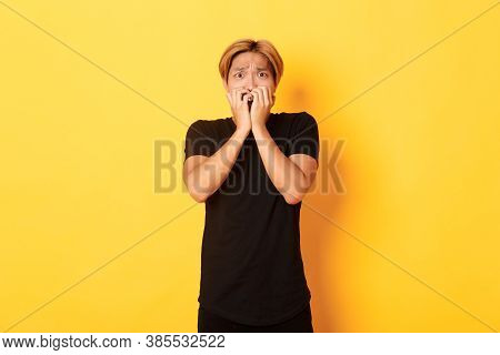 Portrait Of Scared Insecure Asian Blond Guy, Holding Hands Over Mouth Horrified, Looking Frightened,