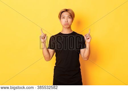 Portrait Of Sulking Gloomy Asian Guy Looking Disappointed, Pointing Fingers Up, Yellow Background