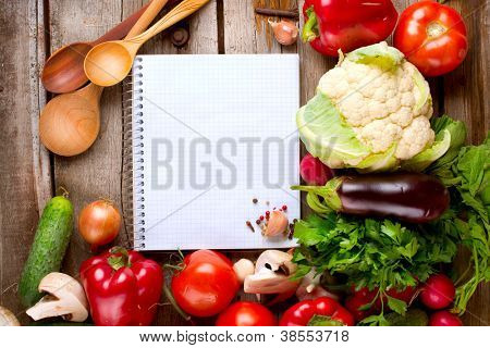 Vegetables and Spices on a Wooden Background and Paper for Notes.Open Notebook and Fresh Vegetables Background.Diet.Dieting.Space For Your Text
