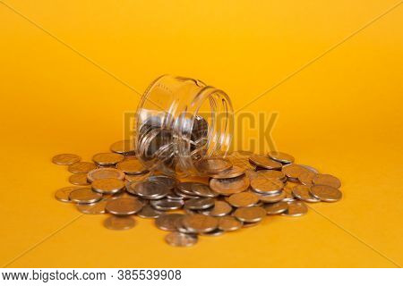Save Finances By Accumulating Them. Glass Jar On A Yellow Background